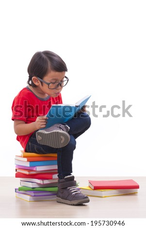 Cute boy reading a book while sitting on books  - stock photo