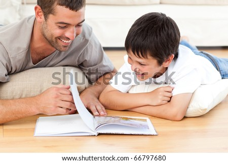 Cute boy reading a book with his father on the floor at home - stock photo