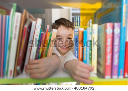 Cute boy reading book in library    - stock photo