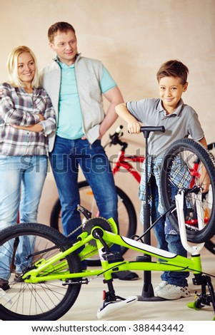 Cute boy repairing his bicycle himself with his parents standing behind - stock photo