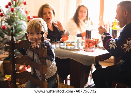 Cute boy sitting at the table enjoying his christmas meal