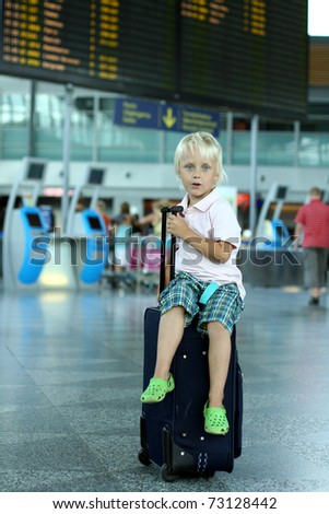 Cute boy sitting on baggage at the airport - stock photo
