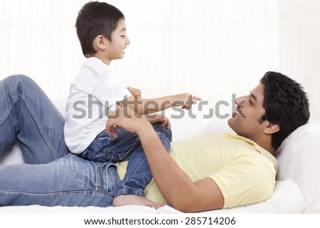 Cute boy sitting on father at home - stock photo