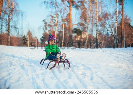 cute Boy Sledging In park - stock photo