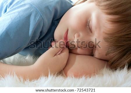 Cute boy sleeping on white fur. Sleep well. - stock photo