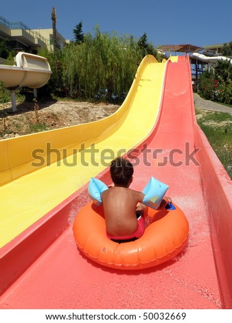 cute boy sliding head down on yellow water slide