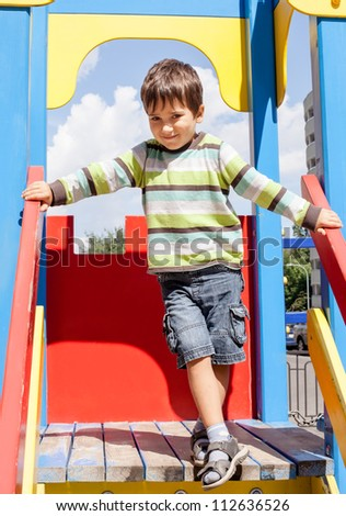 cute boy standing on playground - stock photo