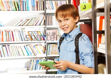 Cute boy stands and holds books in library - stock photo