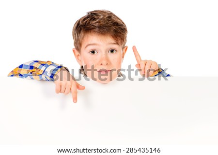 Cute boy stands behind a white board. Copy space. Isolated over white. - stock photo