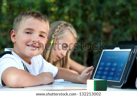 Cute boy student showing maths homework on tablet outdoors. - stock photo