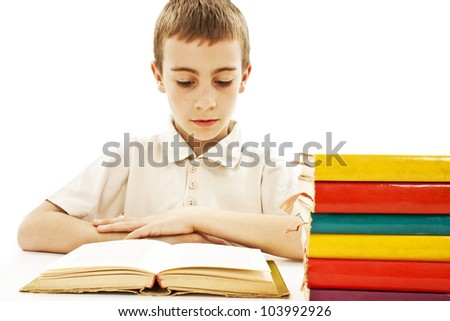 Cute boy studying and reading a book on his desk. Isolated on white background. - stock photo