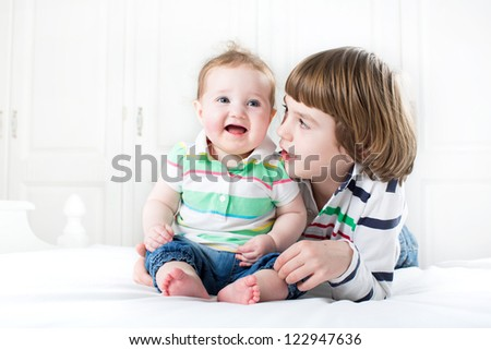 Cute boy talking to his baby sister - stock photo