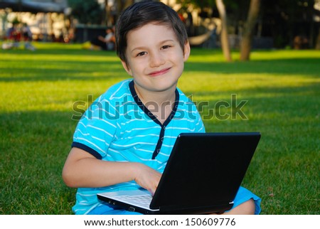 Cute boy typing on laptop computer, resting outdoor / Child Boy using laptop