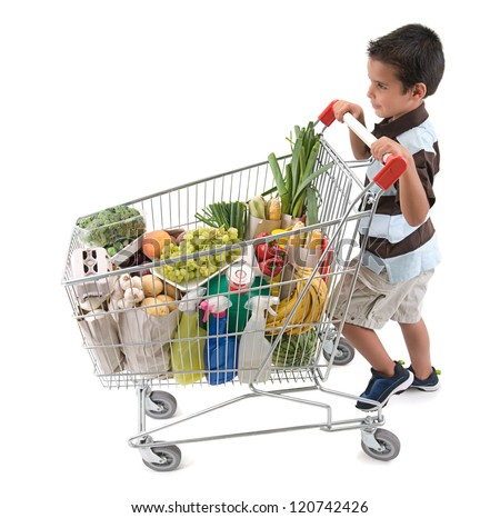 Cute boy walking with shopping trolley isolated on white - stock photo