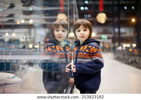 Cute boy, watching some toys at the airport, while waiting for his plane to departure, Christmas trip - stock photo