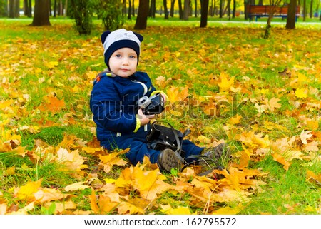 Cute boy with a film camera sits on fallen leaves in the Park. Autumn season - stock photo