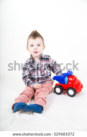 Cute boy with a mohawk on his head, in a plaid shirt and pink pants plays with a plastic toy car on a white background
