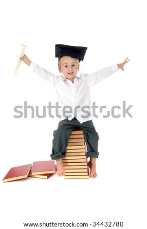 Cute Boy with arms in air waves diploma and wears graduation cap while sitting on stack of books - stock photo