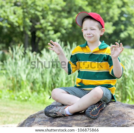Cute boy with big smile meditating outdoors portrait - stock photo