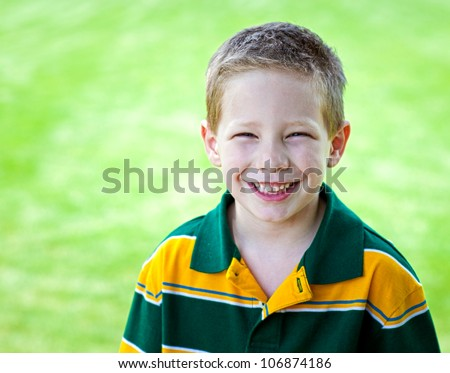 Cute boy with big smile outdoors portrait - stock photo
