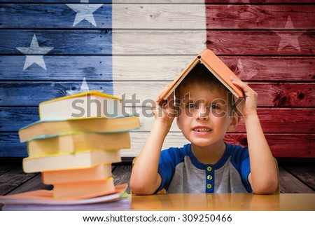 Cute boy with book on head against composite image of usa national flag - stock photo