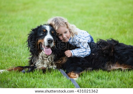 cute boy with curly blonde hair embraces a bernese mountain dog  - stock photo