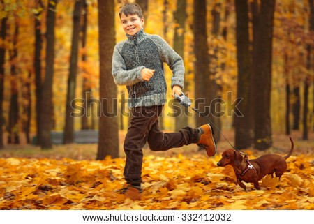 Cute boy, with dog (dachshund), running in the autumn park. - stock photo