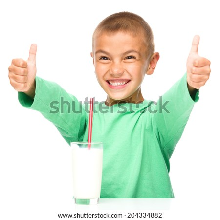 Cute boy with glass of milk is showing thumb up sign using both hands, isolated over white - stock photo