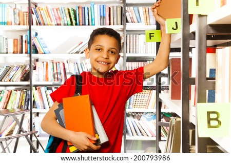 Cute boy with hand on bookshelf holds many books - stock photo