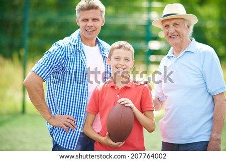 Cute boy with rugby ball and his grandfather and father looking at camera outdoors - stock photo