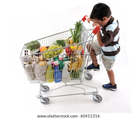 Cute boy with shopping cart full of grocery isolated on white background - a series of SHOPPING TROLLEY images. - stock photo