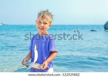 Cute boy with toy ship in hands ashore. Vertical view - stock photo