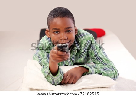 Cute boy with TV remote changing channel - stock photo