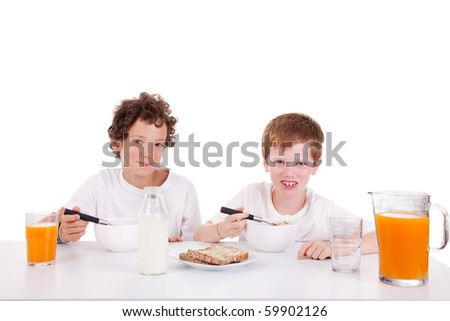 cute boys taking breakfast, isolated on white, studio shot - stock photo