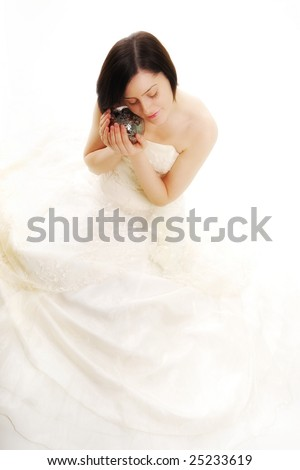 Cute bride touching her face to a magic silver ball in a high key light - stock photo
