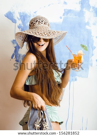 cute bright woman in sunglasses and hat with cocktail in bikini in studio