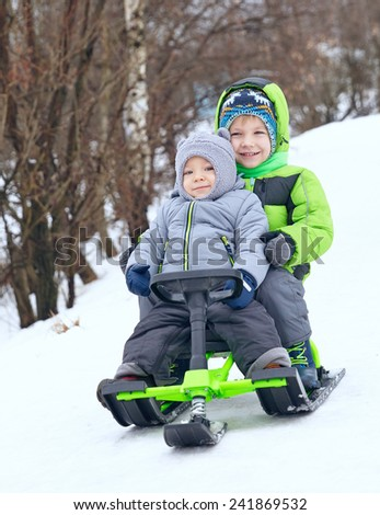 Cute brothers on sleigh in snow park - stock photo