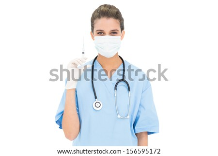 Cute brown haired nurse in blue scrubs wearing a protective mask and holding a syringe on white background - stock photo