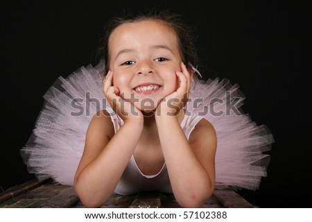 Cute brunette ballet girl wearing a pink ballet costume - stock photo