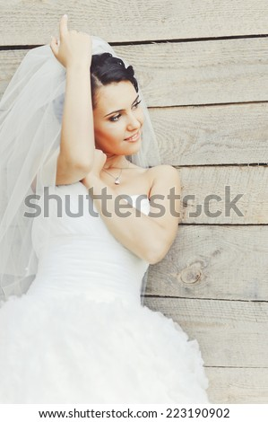 Cute brunette caucasian bride in white dress. Long veil.  - stock photo
