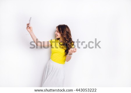 Cute brunette girl listening to music on earphones on smartphone is having fun and takes a selfie. She smiles widely. She has long wavy brunette hair. She wears yellow t-shirt and white skirt. - stock photo