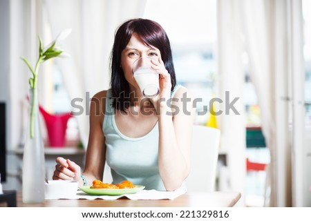 Cute brunette having breakfast and drinking milk, at home - stock photo