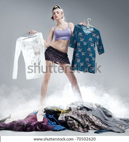 Cute brunette holding clothes - stock photo