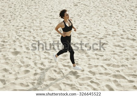 cute brunette in black sport outfit is running on the autumn river beach. She is in leggings, top and white sneakers. Sun is shining.  - stock photo