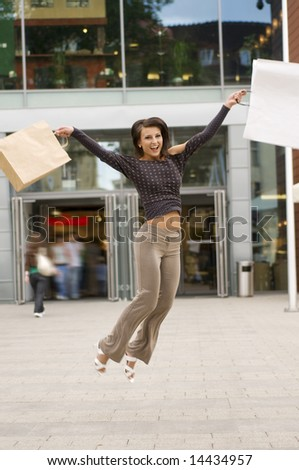 cute brunette jumping for joy in front of a commercial center after shopping