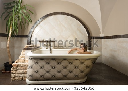 cute brunette sitting relaxed in a bathtub in elegant rustic bathroom in a luxury spa, smiling and looking in camera.  - stock photo