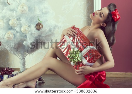 cute brunette woman in erotic pose sitting near christmas decorated tree and covering her naked breast with big gift box. wearing red ribbon at waistline  - stock photo