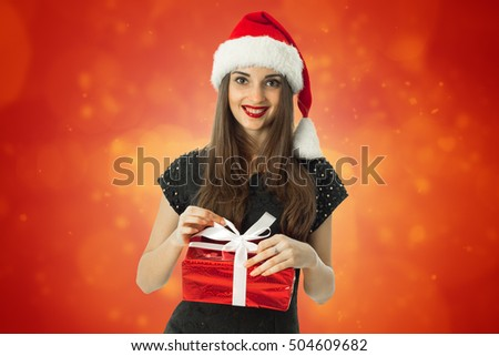 cute brunette woman in santa hat smiling with red gift in hands on red background