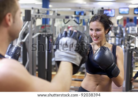 Cute brunette woman training with boxing gloves at the gym - stock photo