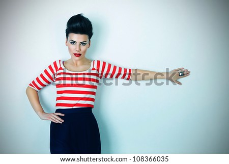 cute brunette woman with hand on wall